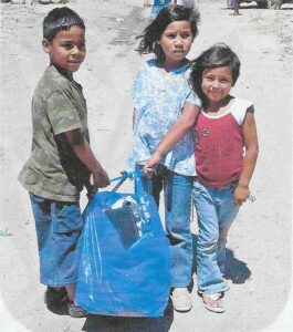 3 kids with a bag